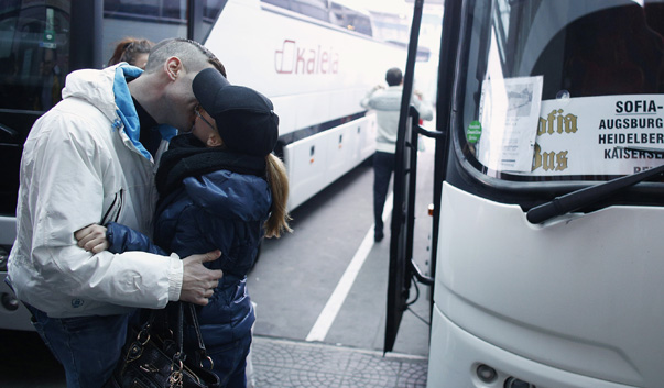 A couple kiss goodbye next to a bus departing from Sofia's central bus station, headed to London via Austria, Germany and France