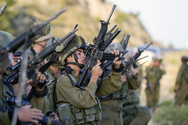 Israeli soldiers load their weapons near Hebron