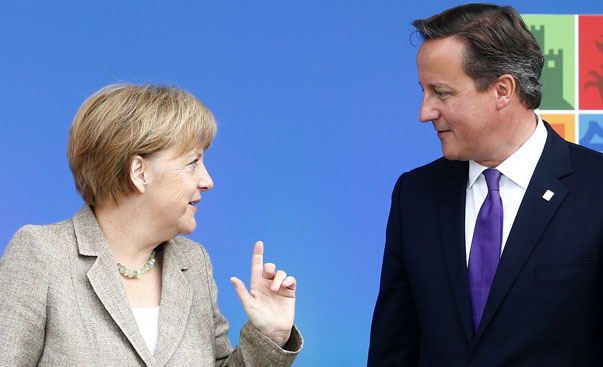 Britain's Prime Minister David Cameron greets German Chancellor Angela Merkel at the start of the  NATO summit at the Celtic Manor resort, near Newport