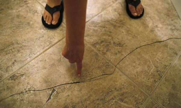 Mary Mahan points to a crack in the floor tile of her home that was a result of an earthquake in Wooster, Arkansas