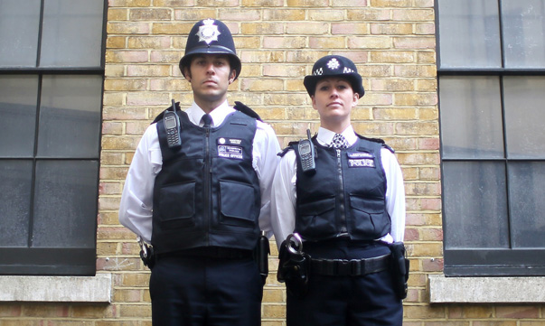 Police constables pose for a photograph wearing their Metropolitan Police beat uniforms, in London