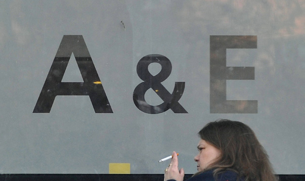 A woman smokes a cigarette outside an Accident and Emergency entrance at an NHS hospital in London
