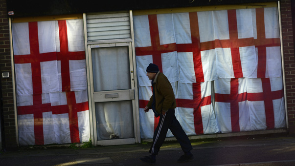 Man walks past a shop decorated with some flags of St. George in Cliftonville