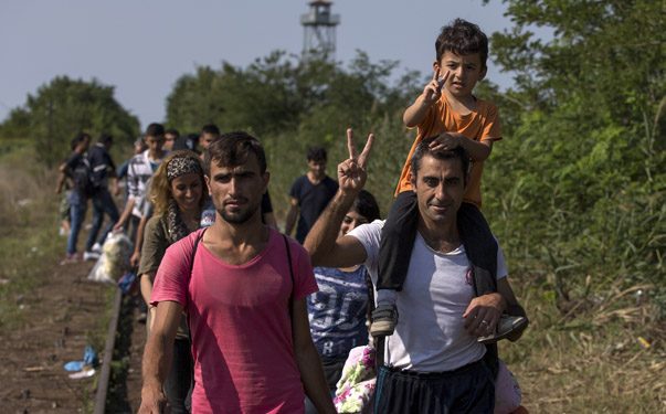 Syrian migrants walk along a railway track to cross the Serbian border with Hungary near the village of Horgos